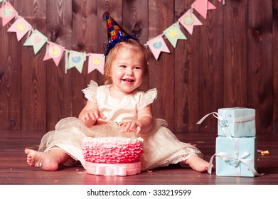 Laughing baby girl 1 year old eating birthday cake in room. Wearing princess dress. First birthday celebration.