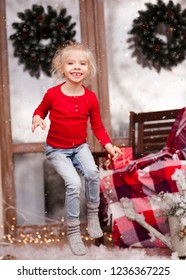 Laughing baby girl jumping over Christmas decor. Looking at camer.a Happiness.