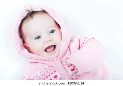 Laughing baby girl wearing a knitted pink sweater with red hearts
