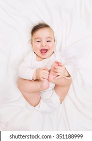laughing baby lies on the bed