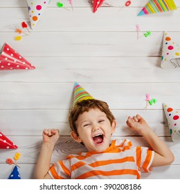 Laughing baby lying on the wooden floor with festive caps and candles on a carnival party. Healthy smiling, Happy childhood concept.