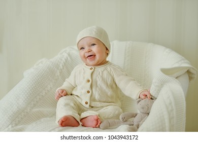 laughing baby wearing knitted suit is sitting on the chair