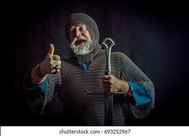 Laughing bearded knight with the sword on the dark background