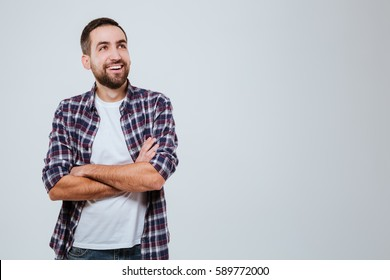 Laughing Bearded man in shirt which posing with crossed arms and looking away