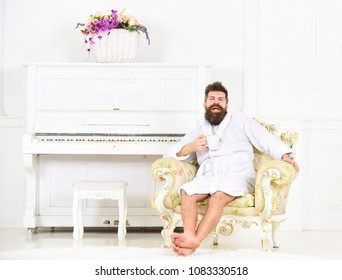 Laughing bearded man sitting in beautiful room with antique furniture and white piano. Smiling guy drinking coffee or tea. Millionaire having breakfast. Perfect morning concept.