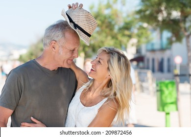 Laughing beautiful affectionate woman giving her husband her trendy hat as they enjoy a summer vacation at the coast