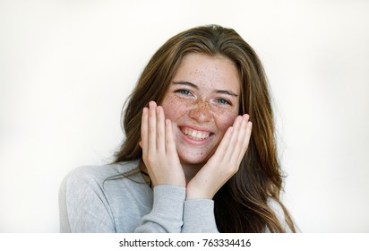 Laughing beautiful girl with freckles on face and happy eyes with surprise selling hands to face against white wall background. Positive emotions and happiness concept. European woman. Positive.