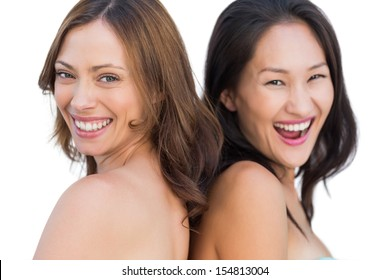 Laughing beautiful nude models posing back to back on white background