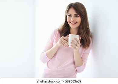 Laughing beautiful woman with cup of coffee on white background. Copy space