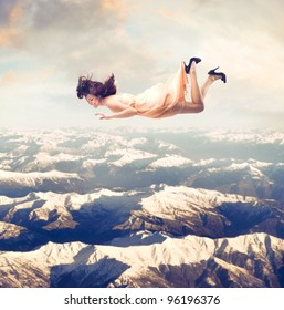 Laughing beautiful woman flying over the mountains