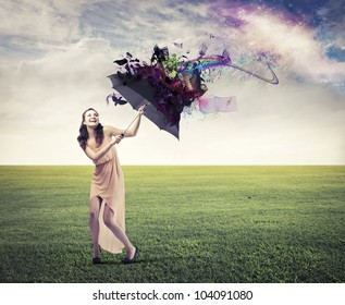 Laughing beautiful woman on a green meadow sheltering from the rainbow under an umbrella