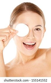 Laughing beautiful young woman holding a round white cotton pad to her eye  close up portrait with bare shoulders