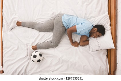 Laughing black sport fan sleeping with soccer ball, dreaming about playing football, top view