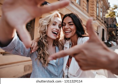 Laughing blithesome woman with dark hair walking down the street with friend. Carefree blonde girl posing on city background.