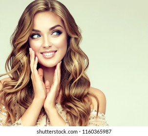 Laughing blonde girl with long  and   shiny wavy hair .  Beautiful  smiling woman model with curly hairstyle .