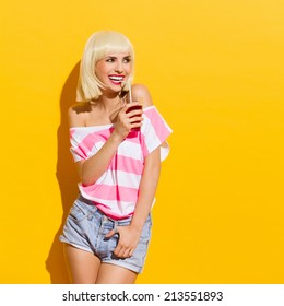 Laughing blonde young woman holding red drink and looking away. Three quarter length studio shot on yellow background.