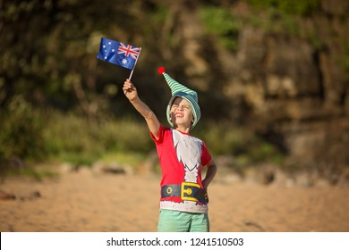 A laughing boy of 8 years old an elf hat on a sandy beach with Australian flag in hands with bushes in the background with Australian flag in hands