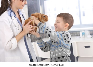 Laughing boy getting back cute pet rabbit from veterinary at pets' clinic.