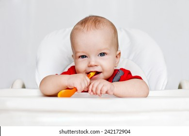 laughing boy holding a spoon on a white background