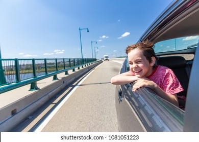 laughing boy looking out of car window. happy child in the back seat of the car enjoying the view from the window. The concept of freedom, school vacations or holidays. Copy space for your text