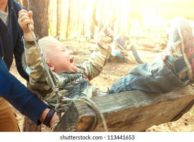 Laughing boy on swing