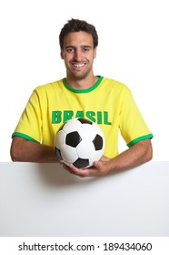 Laughing brazilian soccer fan with ball behind signboard