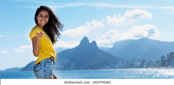 Laughing brazilian woman with curly long hair at Ipanema beach at Rio de Janeiro with beach in summer