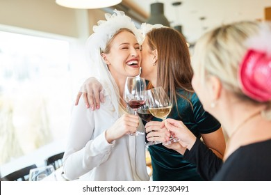 Laughing bride with bridal veil is hugged by girlfriend in the restaurant