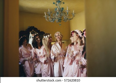 Laughing bride and bridesmaids in silk robes stand under blue chandelier