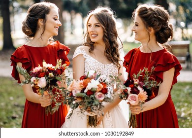 Laughing bride and bridesmaids tell funny stories standing on footsteps outside