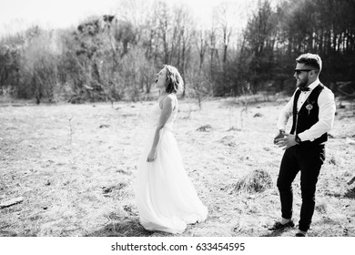 Laughing bride walks from groom on the lawn