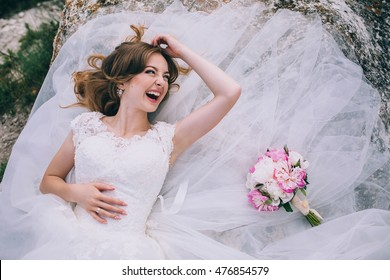 Laughing bride in white lace dress