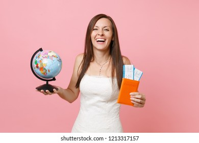 Laughing bride woman in white wedding dress holding world globe, passport boarding pass ticket going abroad for honeymoon, vacation isolated on pastel pink background. Wedding celebration. Copy space