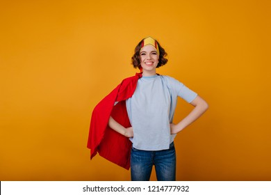 Laughing brunette girl in superhero outfit posing on yellow background. Joyful lady enjoying masquerade and posing in princess attire.