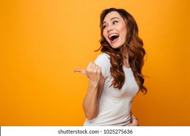 Laughing brunette woman in t-shirt looking and pointing away with thumb over yellow background