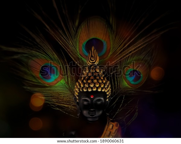 laughing buddha idol with peacock feather in the background.peaceful smiling buddha statue edited with bokeh lights.beautiful background image of buddha in calm meditated state.peaceful backgrounds