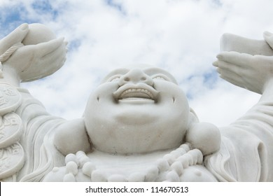 Laughing Buddha isolated against the bright sky