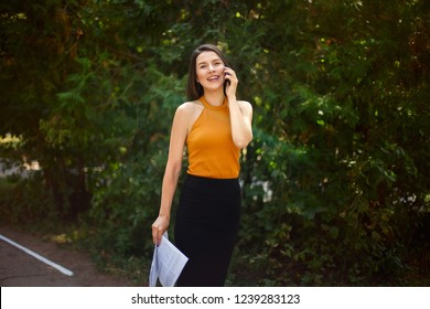 laughing business lady talking on the phone with papers and documents in her hands in nature