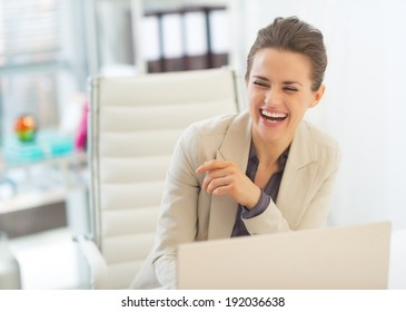 Laughing business woman with laptop