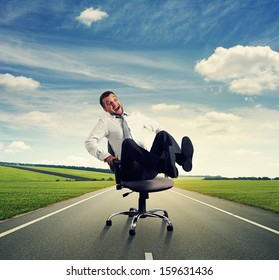 laughing businessman sitting on the office chair and rolling on the road