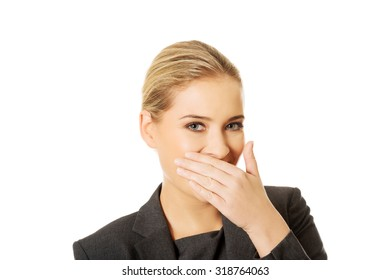 Laughing businesswoman covering her mouth.