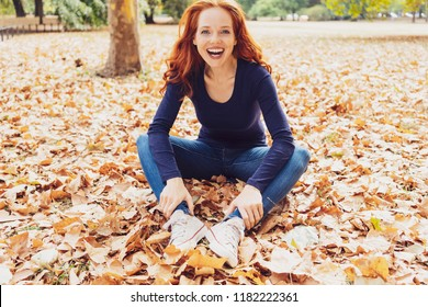 Laughing carefree young woman in a fall park sitting on the ground amongst the autumn leaves looking at the camera
