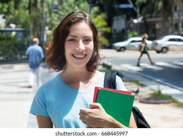 Laughing caucasian female student in the city