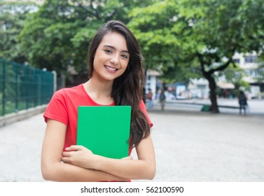 Laughing caucasian female student with red shirt in the city