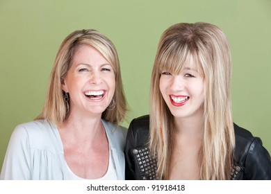 Laughing Caucasian mom and daughter over green background