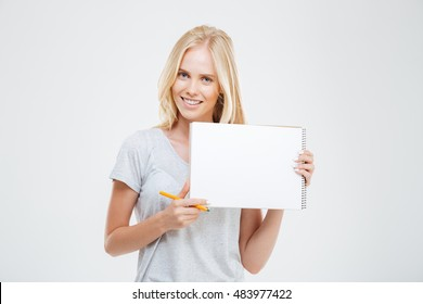 Laughing cheerful pretty girl showing blank notebook isolated on the white background