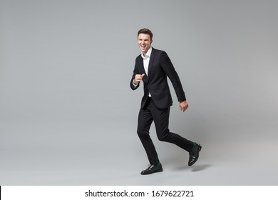 Laughing cheerful young business man in classic black suit shirt posing isolated on grey wall background studio portrait. Achievement career wealth business concept. Mock up copy space. Running