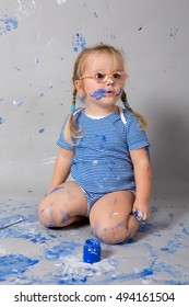 Laughing child with blue paint dots on face with colors and brushes sitting on floor.