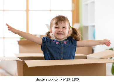 Laughing child girl sitting in cardboard box in her new home