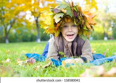 Laughing child lies on a grass in a wreath from maple leaves